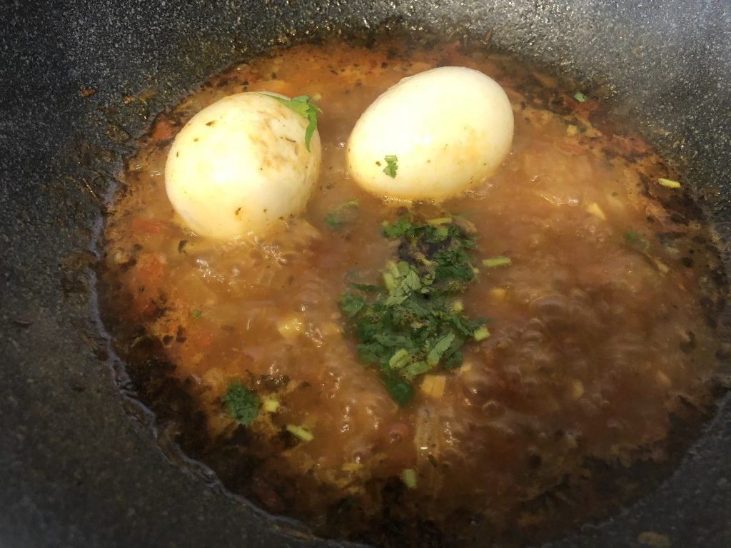 Add boiled and peeled eggs and coriander to the egg curry